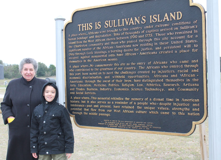 My grandson and I standing by the sign on Sullivan's Island.