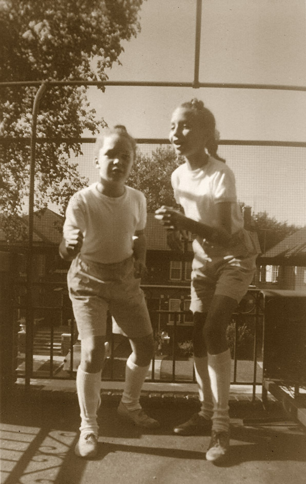Pearl and Kristin pretending to race on the upper front porch. Notice the well kept houses in the background.