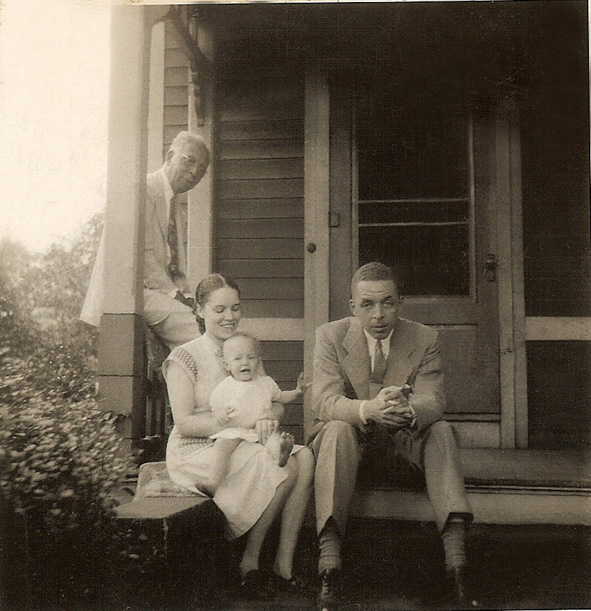 My paternal grandfather, Dr. Albert B. Cleage Sr. sitting on the railing. My mother, Doris Graham Cleage, holding me. My father Rev. Albert B. Cleage Jr. Summer of 1947 on the back porch of the house on King street.