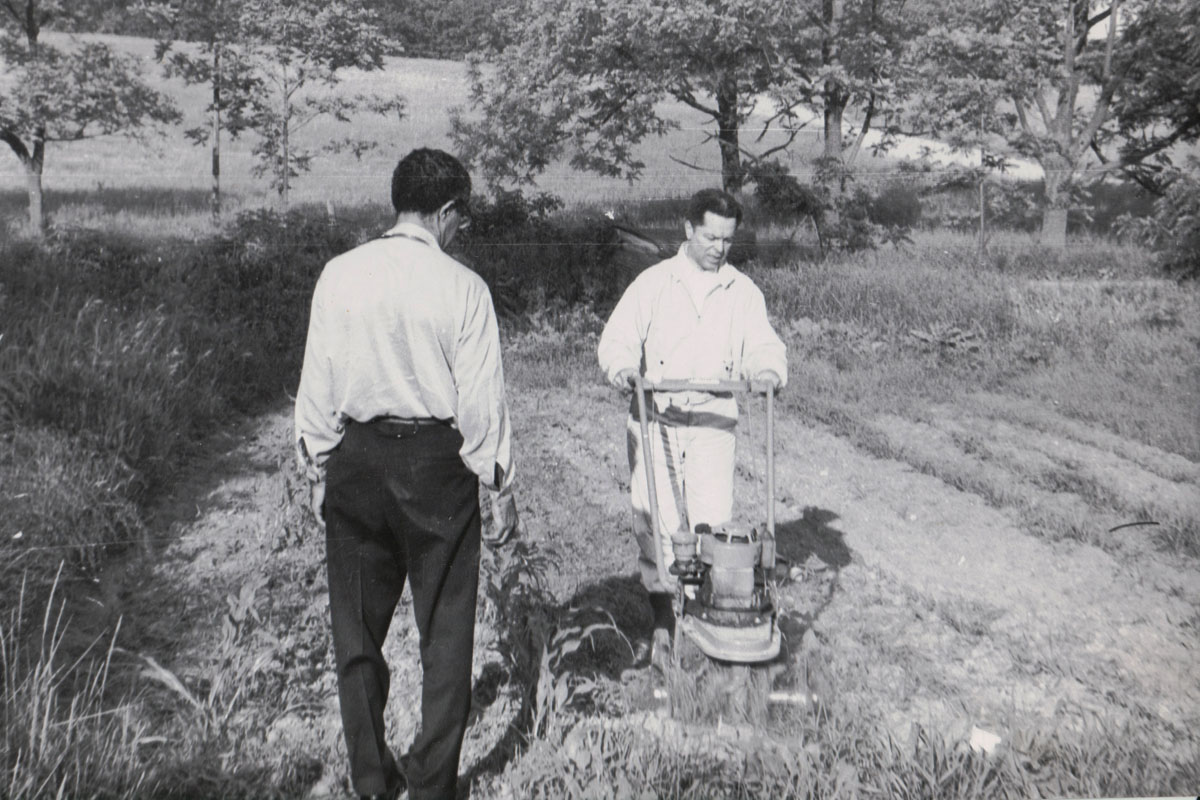 Henry Cleage rotilling the garden at Old plank which Hugh Cleage watches.