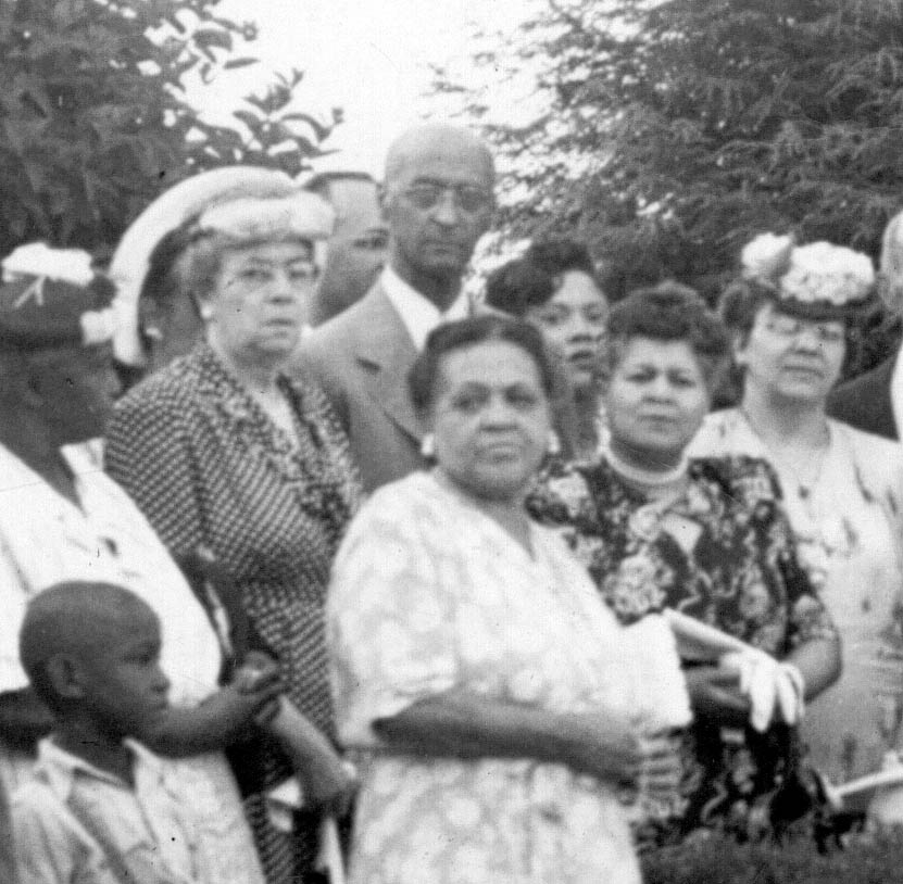 Gertrude Cleage (wife of Uncle Jake) with feathered hat, next to her is Henry Cleage and in front of him in the dark flowered dress is his wife, Ola Cleage.