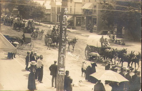 Buffalo Soldiers driving wagons through town.