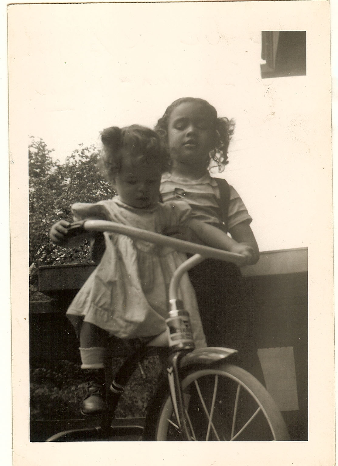 My cousin Barbara on a bike around 1949. Her older sister Dee Dee is holding her up.